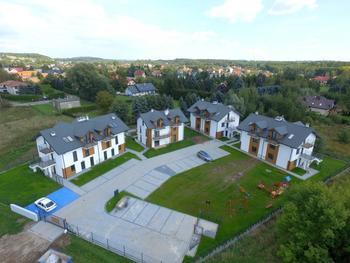 """Naszą pierwszą zrealizowaną inwestycją jest osiedle """"Tyniecka Park"""" w Krakowie, zlokalizowane w jednej z najbardziej urokliwych i zielonych części Krakowa. Cała inwestycja składa się 14 lokali mieszkalnych wraz z zewnętrznymi miejscami postojowymi. Klienci mogli liczyć na fachową obsługę w każdym zakresie, co przełożyło się na 100% sprzedaż mieszkań, zadowolenie i satysfakcję lokatorów. Inwestycja realizowana była w latach 2017-2019. Doskonałe ułożenie działki, doskonałe widoki z każdego z projektowanych mieszkań, świetny układ pomieszczeń wyróżniają inwestycję. Całe osiedle mieści się na dużej ponad 30-arowej działce, na której znajdują się indywidualne ogródki jak również teren przeznaczony do wspólnego użytkowania."""